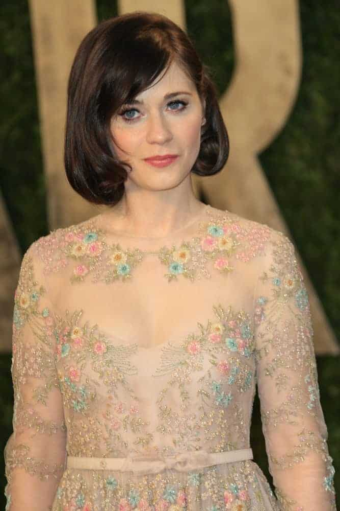 Zooey Deschanel attended the Vanity Fair Oscar Party at Sunset Tower on February 24, 2013, in West Hollywood, California. She was seen wearing a charming floral beige sheer dress with her chin-length dark brunette bob hairstyle with vintage curls and side-swept bangs.
