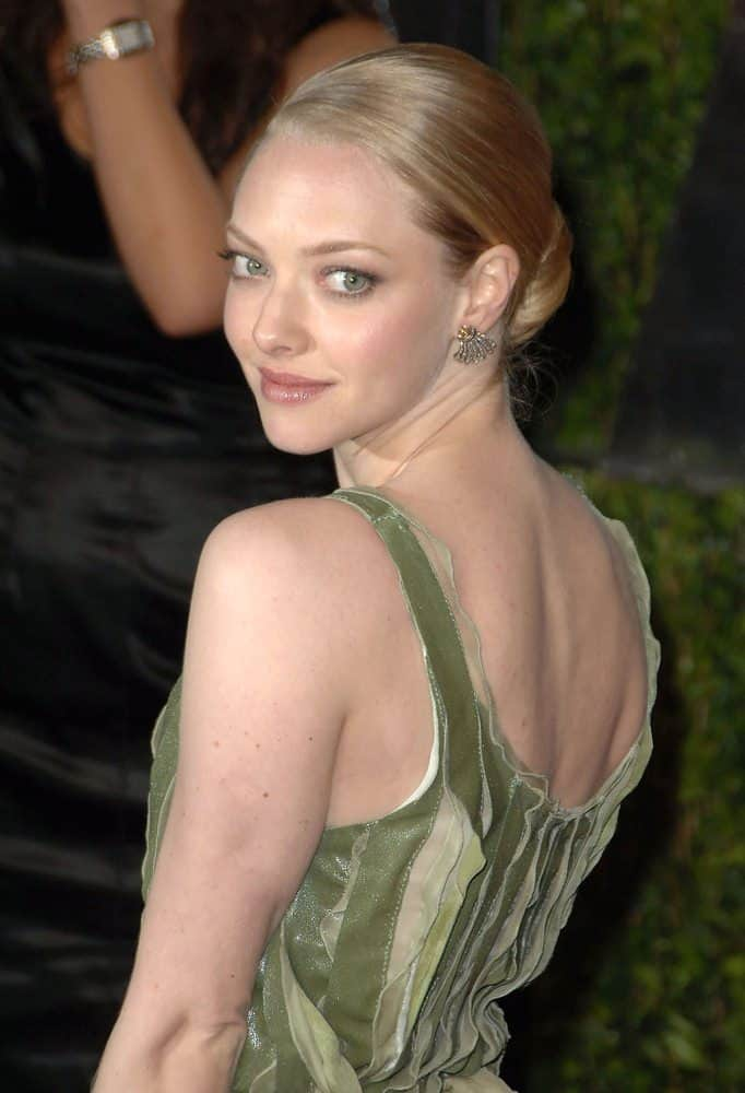 Here's Amanda Seyfried sporting a tight low bun with her infamous long blonde hair.  Looks great with silver earrings and chic green dress.  I love this pose which is a great candid photo of her.  She has a terrific natural smile on her that's engaging the viewer.  It's no wonder she's a top-tier actress the way she exudes such personality in a photo and on the screen.