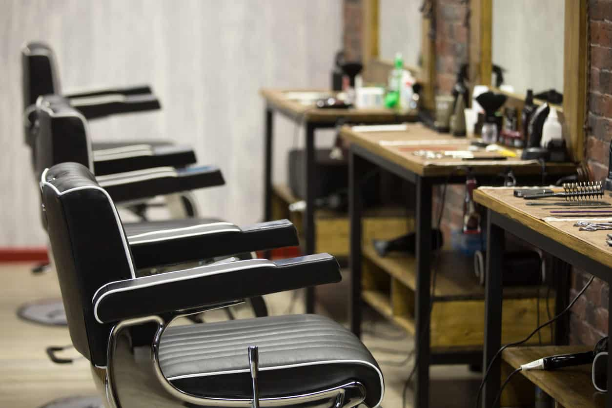 I like the individual barber stations which look aged (probably are) along with mirrors mounted on brick wall. The black and white barber chairs look good too.