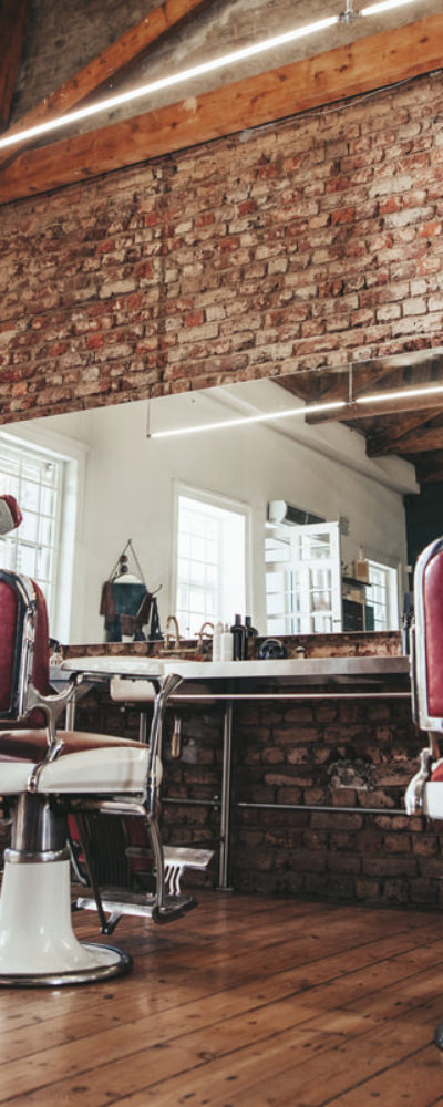 Stunning barber shop interior with tall ceiling, brick wall, old school chairs and wood floor.
