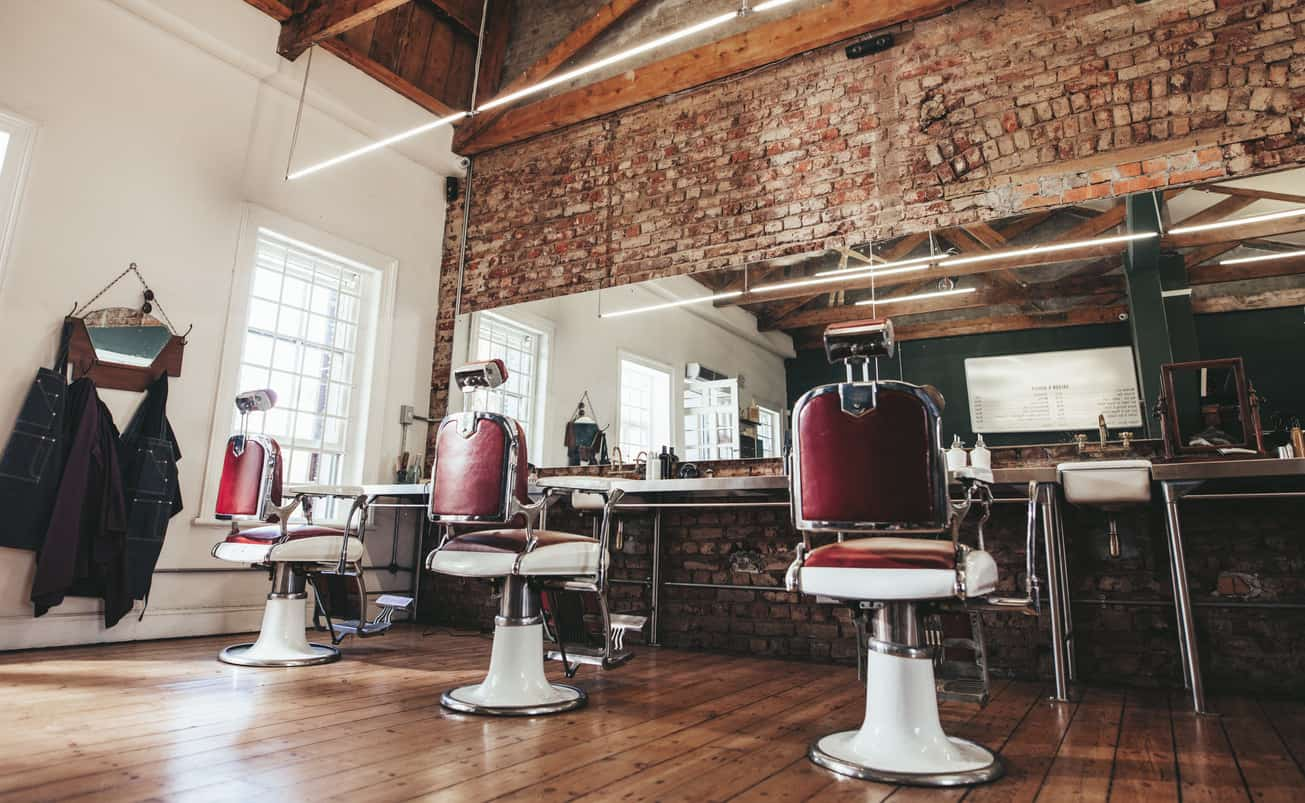 Check out those red and white barber chairs. They are so cool and totally make this barber shop awesome (the brick and wood flooring helps too).