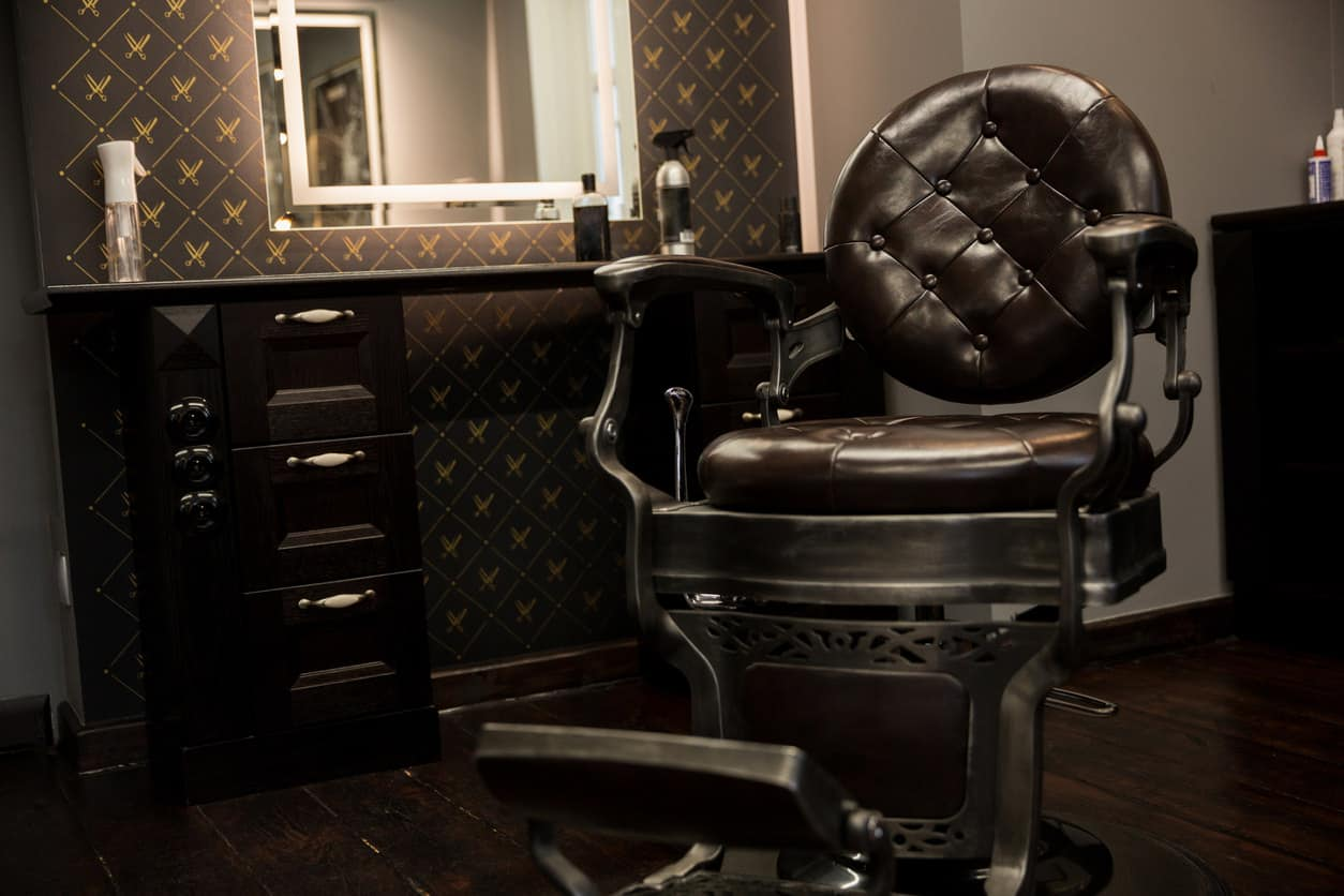Here's a close-up photo of a barber shop cutting station with a beautiful dark brown barber chair with black steel base. The chair sites in front of a dark wood cutting station cabinet. One interesting thing to note is this shop has dark brown patterned wallpaper on the walls which is unusual, but effective.