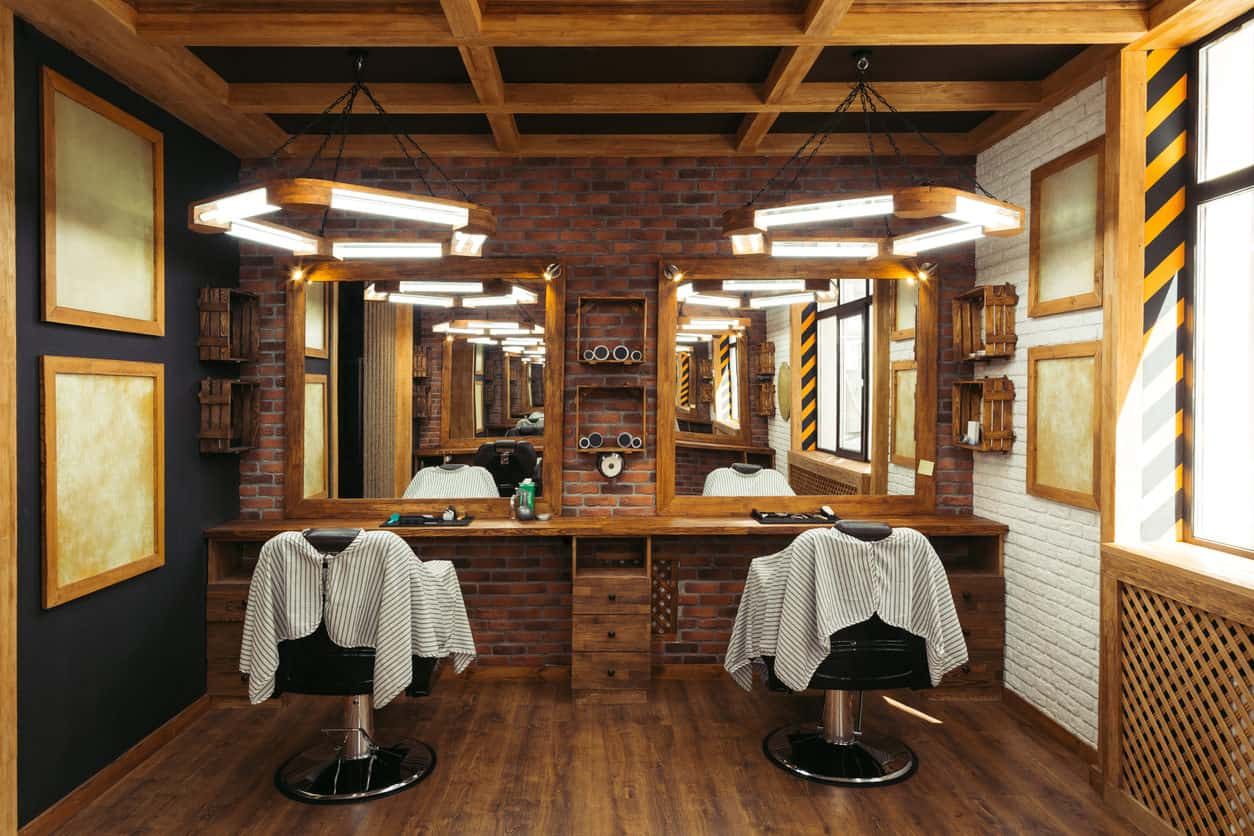 Another rustic, masculine design. I love the suspended wood lights. Those are definitely custom. Check out the coffered beamed ceiling which goes well with the brick and wood flooring. Great design for a small barber shop space.