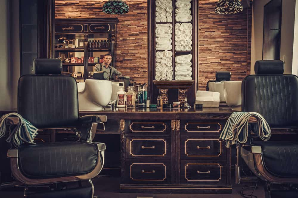 Now we're talking pure vintage old school barber shop design. Look at the detail with those dark cabinet cutting stations along with the old school chairs (which are new, but look old). The brick wall, towel shelf and so much more. This is a truly inspiring barbershop interior.