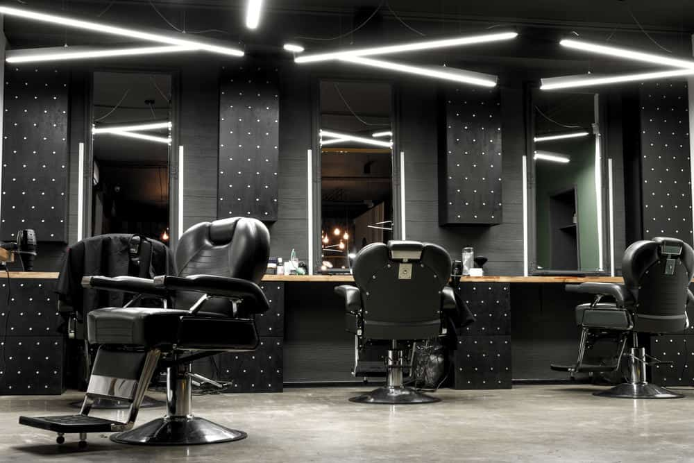 Here's a modern barber shop design. It's very masculine with the black walls and chairs. Check out the Star Wars like lighting. This is definitely a unique barber shop interior look that works well. It's a big difference from the rustic and vintage looking barber shops you so often see.