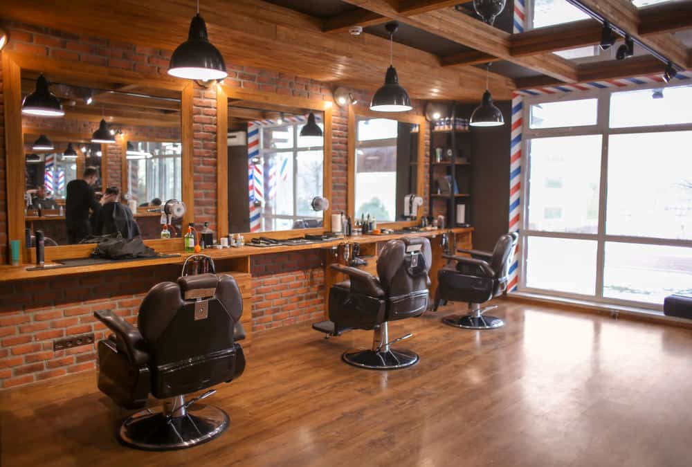 Here's a barber shop in an old building with brick walls and old wood flooring. It's essentially a large empty space with wood flooring, a fantastic floor-to-ceiling window and wood cutting stations. Those chairs are definitely a new but designed to look old school.