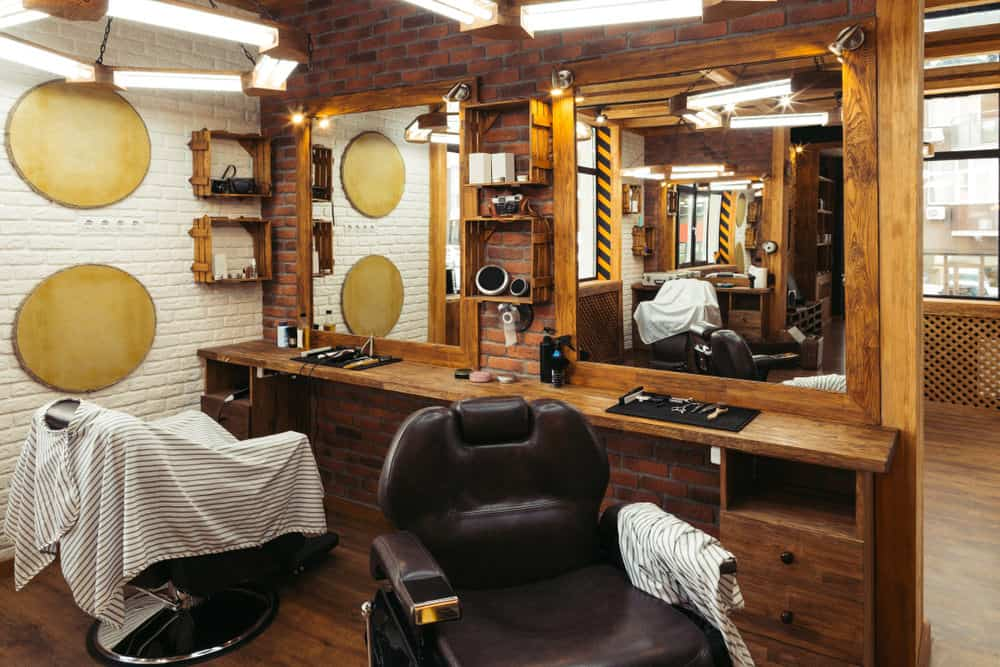Here's an example of a small barber shop design with two chairs. As you can see it's fairly simple with white painted brick wall and then the hair cutting stations are against a dividing brick wall. Simple wood cabinets make up the stations.