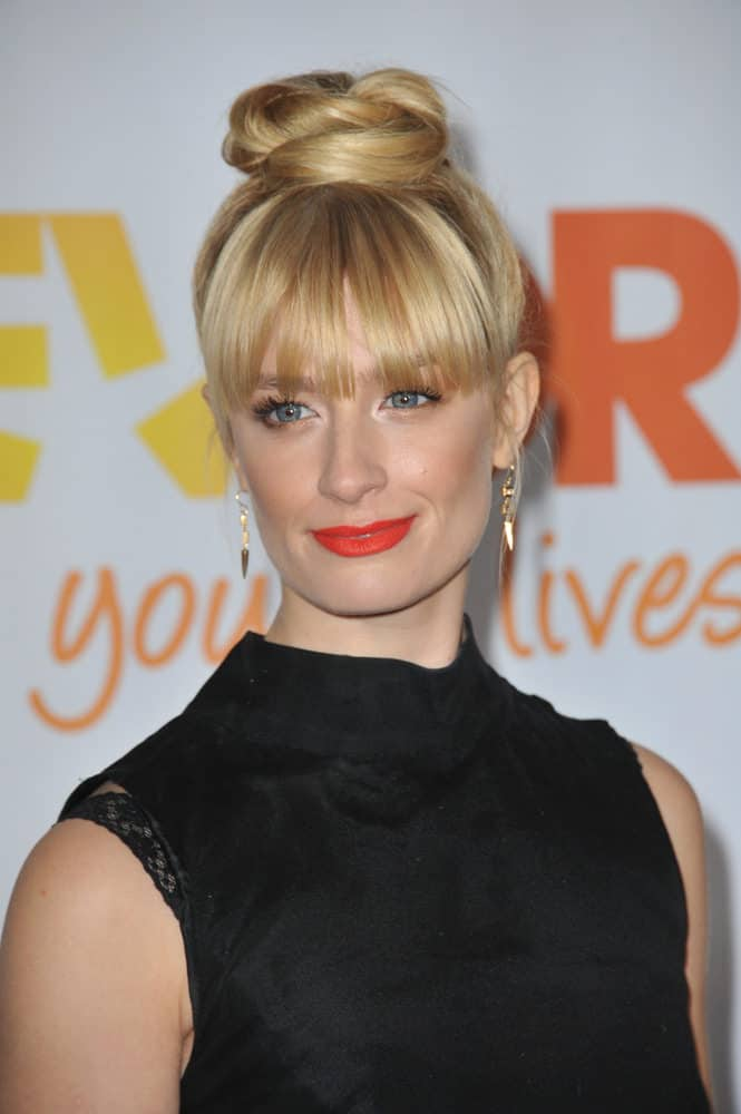 Bangs and buns can go together, especially if you've got eye-grazing fringe like Beth Behrs. The trick is to keep the style sleek. Straighten the hair and pull it up into a very high ponytail. Wrap the ends around into a neat but soft bun.