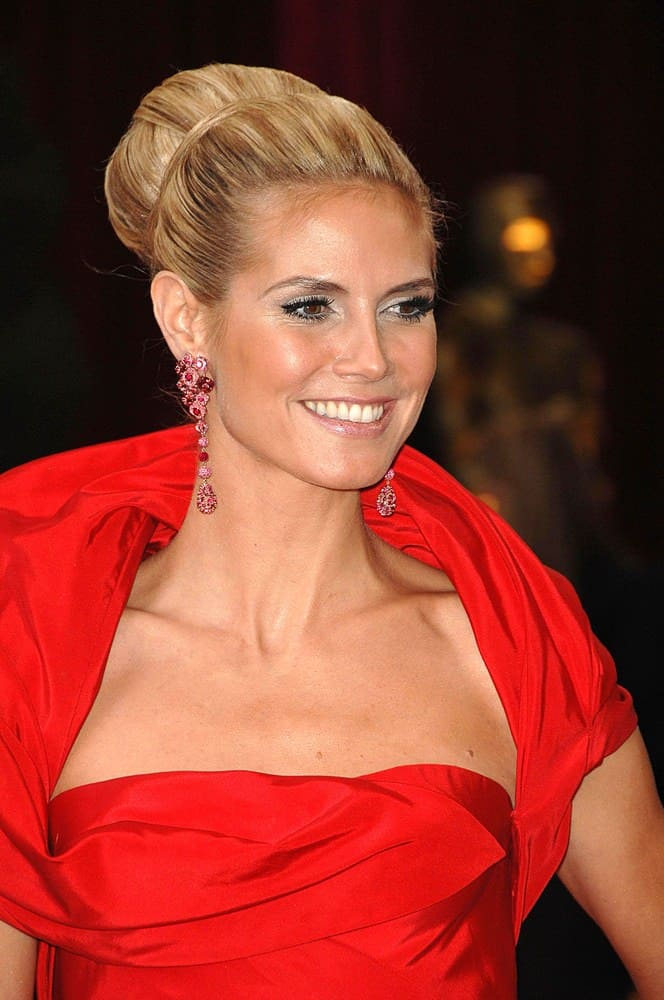 Heidi Klum pulls off this over-the-top elegance with panache! Use a bun ring to create a voluminous, large bun around a ponytail at the crown. Pull out one piece and use it to wrap around the bun once you've got it in place.
