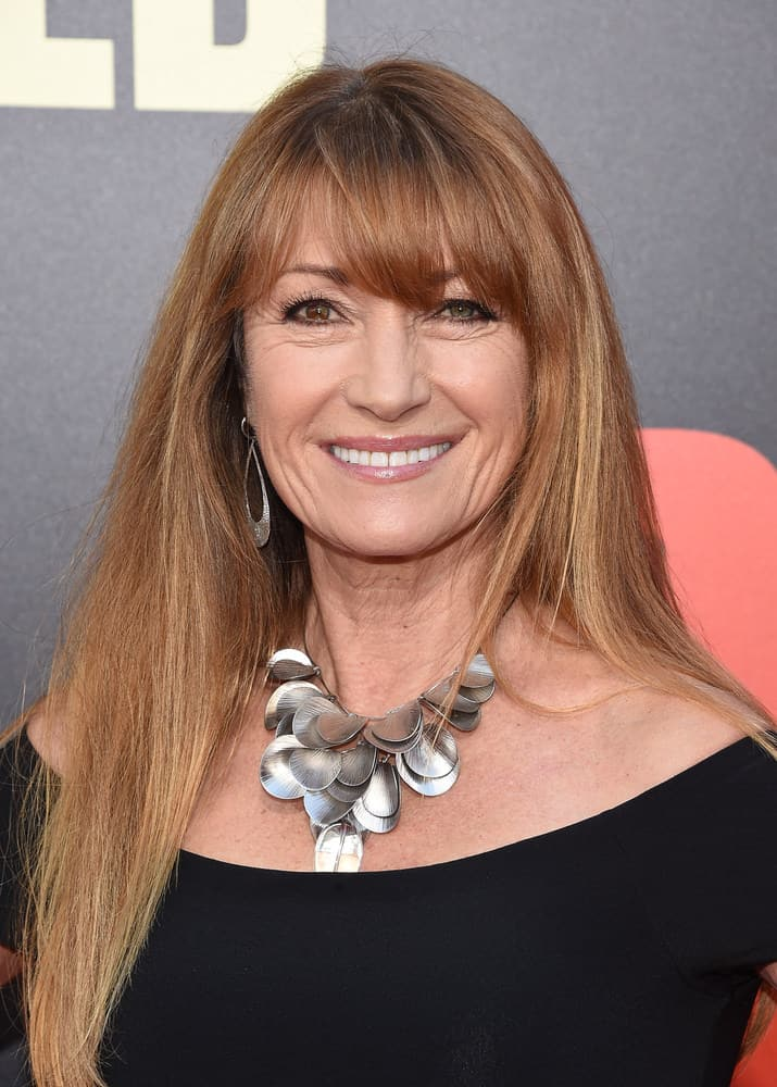 In this style, modeled by celebrity Jane Seymour, long, chestnut-colored hair strands are layered and rest gently on the shoulders of the wearer. The color of the hairstyle shifts from chestnut at the top, to a honey blonde color at the tips of hair strands, resembling a reverse ombre effect. In addition to these colored long layers, side-swept and tapered-cut bangs are included in the hairstyle as a unique supplement.