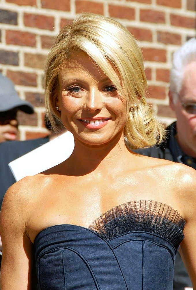 Kelly Ripa's laid-back look goes perfectly with a simple, modern dress. The hairstyle is a low side bun with a smooth, deep side part and a few face-framing pieces pulled out to soften the style.