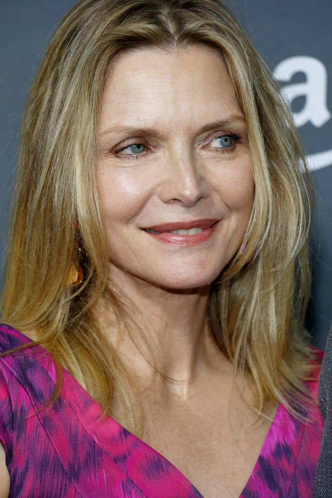 This sixth, simple, but effective hairstyle is modeled by Michelle Pfeiffer. The long-layered style features a light blonde color, with slivers of silver highlights. Along with the long and gently curled layers of hair, a middle part is featured.