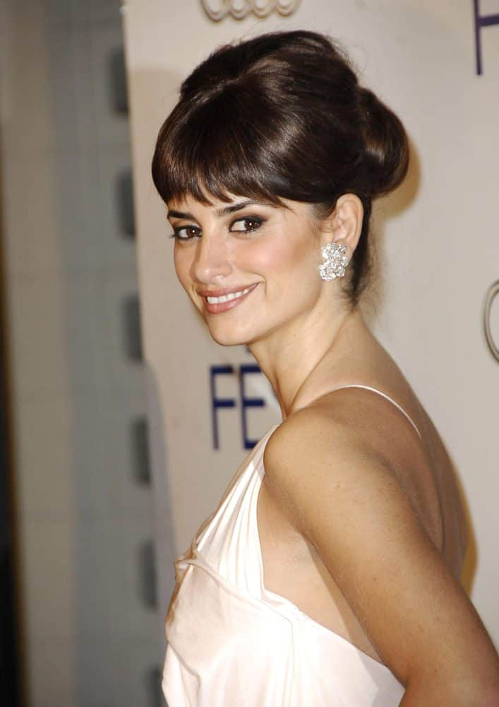Penelope Cruz has timeless style, and the hair to match. Start with plenty of root spray and gently back-comb the crown to get as much volume as possible. Then carefully brush the hair into a bun, taking care not to press down the volume. Finish with a gloss spray.