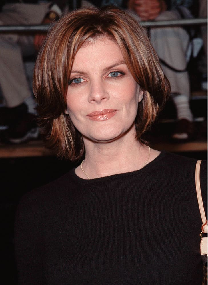 The next hairstyle is portrayed by Rene Russo. Her hairstyle is a mid-length cut that is beautified with auburn and brown-color highlights in order to add dimension to the look of the style. In addition to this multi-dimensional color, the hair is curled towards the back of the face, but the longer, front sections of the hair rest just lightly on Russo's forehead for style purposes.