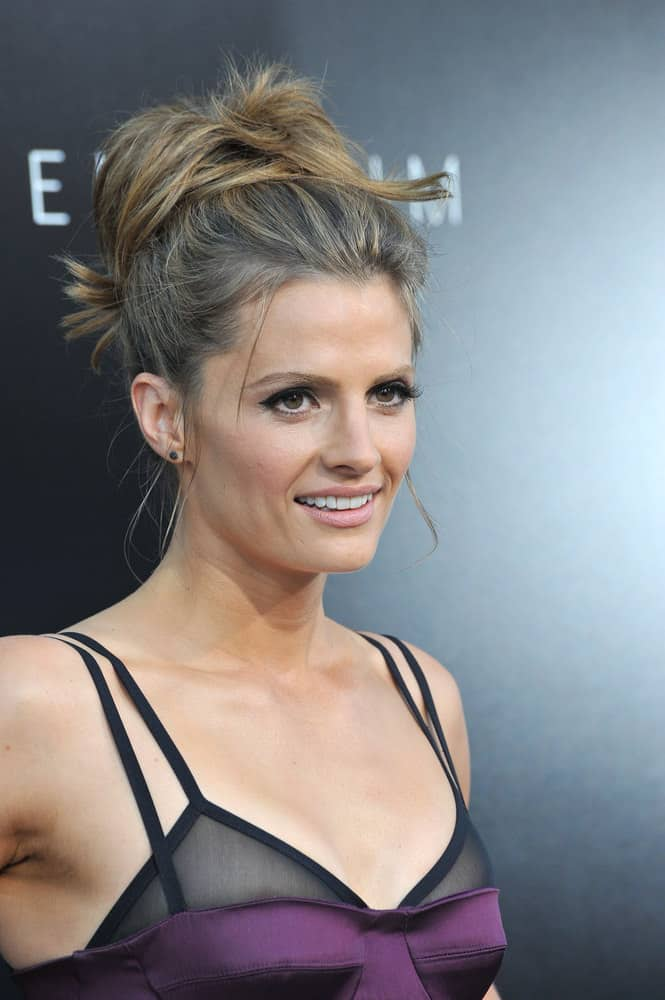 Stana Katic's perfectly undone 'do is part ponytail, part bun, and all style. Finger comb your hair into a high ponytail and loosely wrap into a bun. Tousle the bun and pull out a few pieces. Use a texture paste to separate the ends.