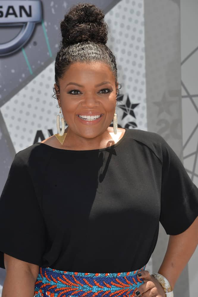 Working with your natural texture can make a beautiful up-do. Take a cue from Yvette Nicole Brown's style and add some moisturizing hair serum before brushing your hair up into a hair tie. Loop your hair through once and wrap the ends around the base. Fan out the loop to finish the look.