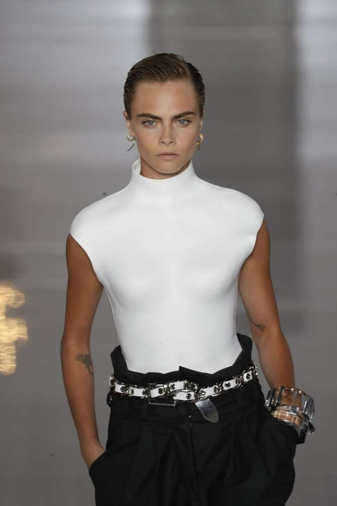 Model and actress Cara Delevingne walked the runway during the Balmain show as part of the Paris Fashion Week Women's wear Spring/Summer 2019 on September 28, 2018, in Paris, France. Her was styled to a slick side-parted finish with a dark brown tone.