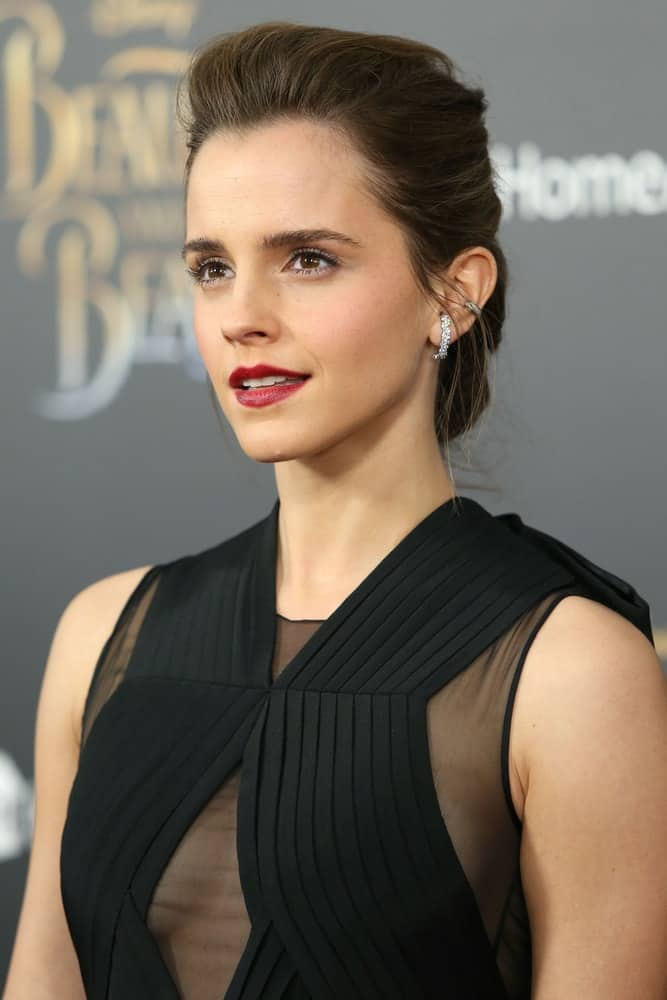 """Emma Watson attended the premiere of """"Beauty and the Beast"""" at Alice Tully Hall on April 13, 2017, in New York City. She wore a classy black sheer dress to pair with her lovely red lips and brushed-back, loose and tousled low bun with a slight pompadour finish."""