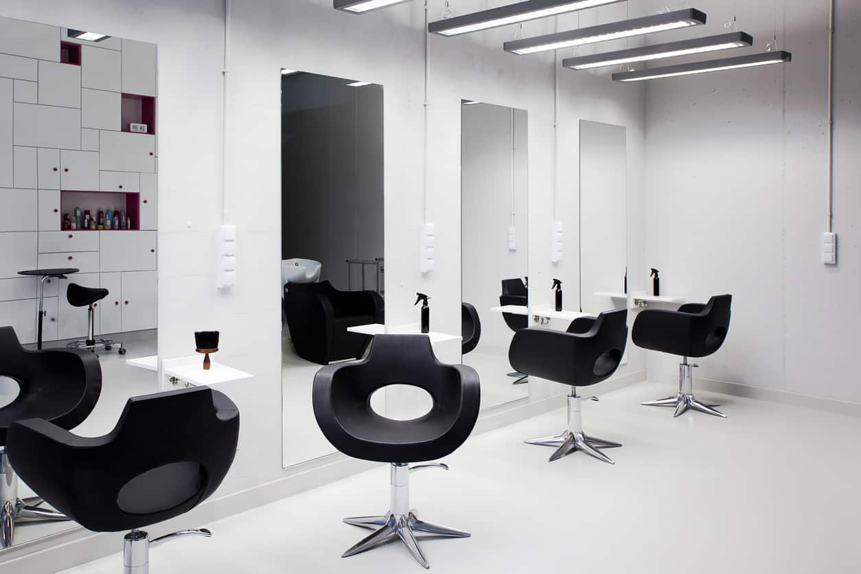 The sharp contrast between black and white paired with the polished look of stainless steel gives this salon a sleek and stylish look. Add some large mirrors, fluorescent lighting, and red accents for a contemporary feel. The glossy red shelves and knobs on the white wall shelf pop and the black seating and the spray bottles on the white floating shelves.
