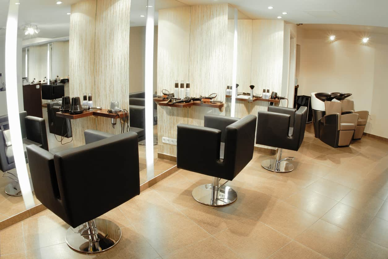 This salon gives off a soft and warm ambiance with the cream colors and wood trim and tables. Paired with square-shaped black chairs with stainless steel bases, this salon has the feel of a 1950s barbershop. The textured wallpaper and flooring adds some interest and keeps it simple. The canister lights help to highlight certain parts of this salon and the white ceiling contrasts with the beige-colored walls and large tiled floor.