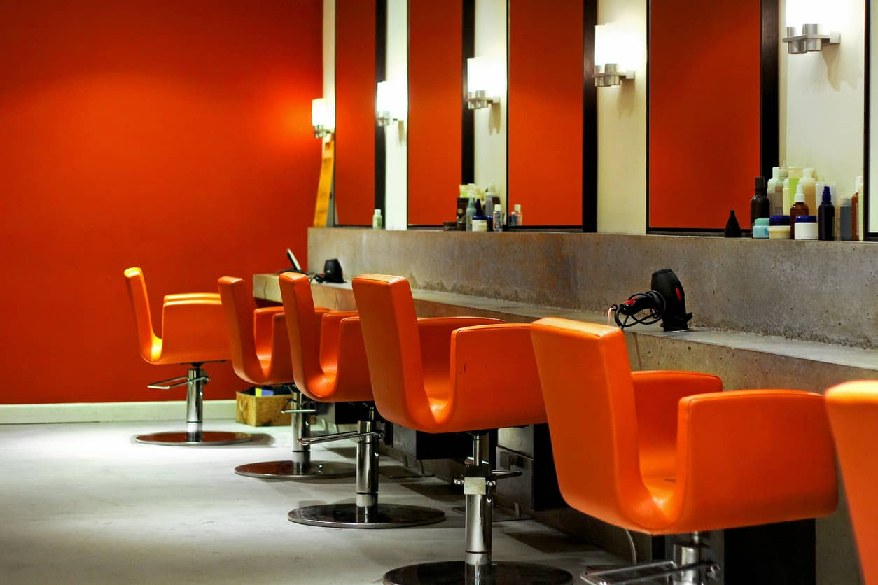 These bright orange chairs and walls of the same color paired with concrete tables and stainless steel light fixtures create a modern look. The concrete floors and black framed mirrors bring this modern look together. It has a warm feel although there is quite a bit of concrete used in this salon.
