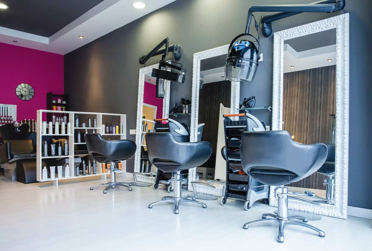 An accent wall is painted neon fuchsia paired with grey-blue walls and pale yellow walls to highlight fun details such as a mirrored clock on the wall. When paired with extra large white chunky framed mirrors in front of grey-blue styling chairs, you have a modern and stylish-looking salon.