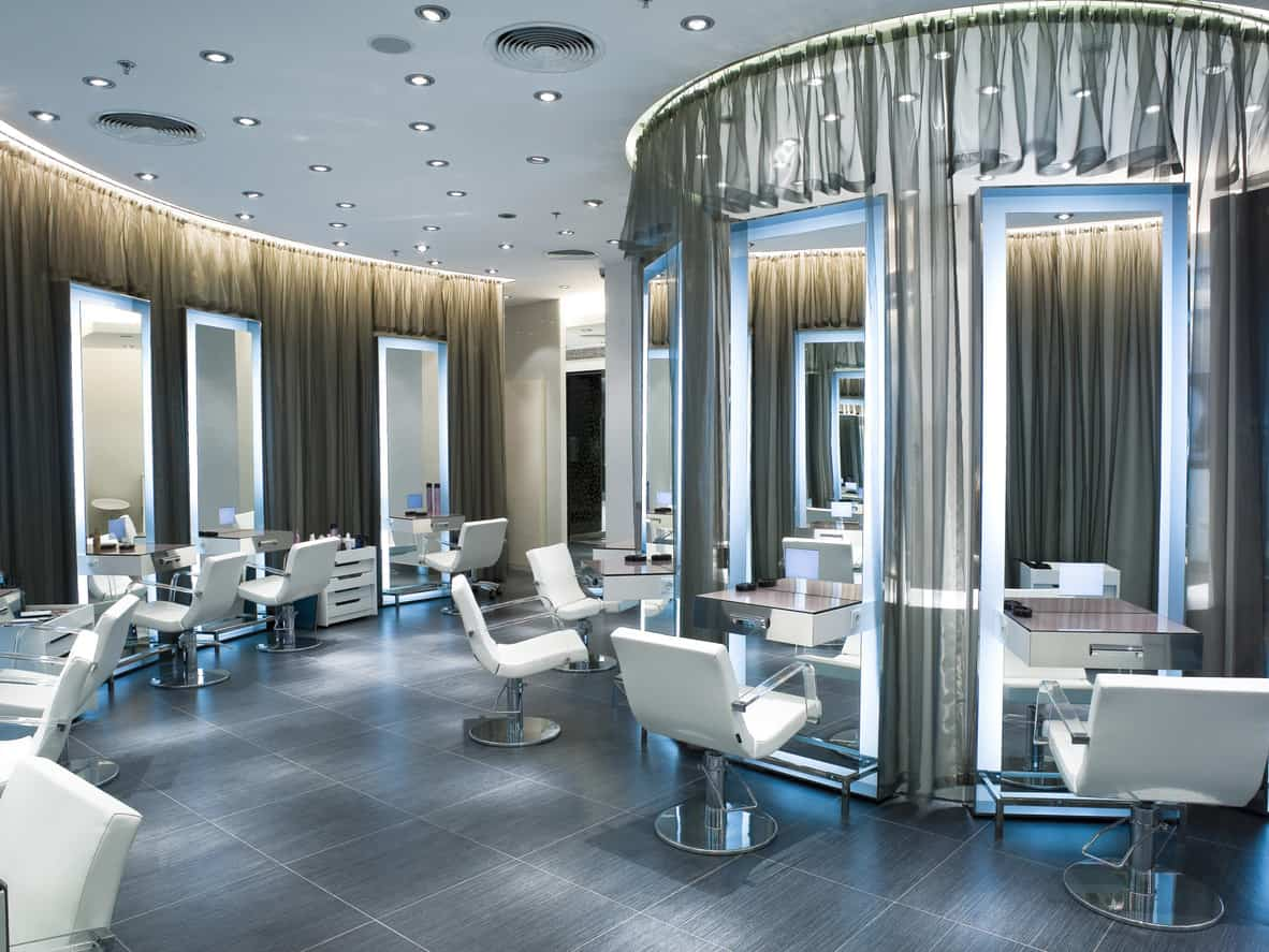 Countless adjustable flush mounted lights dot the ceiling to makes the salon feel like a stage where the customers are the stars. Sheer grey curtains hang from the ceiling, and oversized mirrors are in front of every stylist chair. The chairs are crisp white with see-through bases and armrests for a contemporary design. The mirrors glow with a baby blue light, and the light is reflected off of the semi-glossy grey textured floor. The bases of the chairs and the counters are stainless steel and reflect the light given off by the mirrors.
