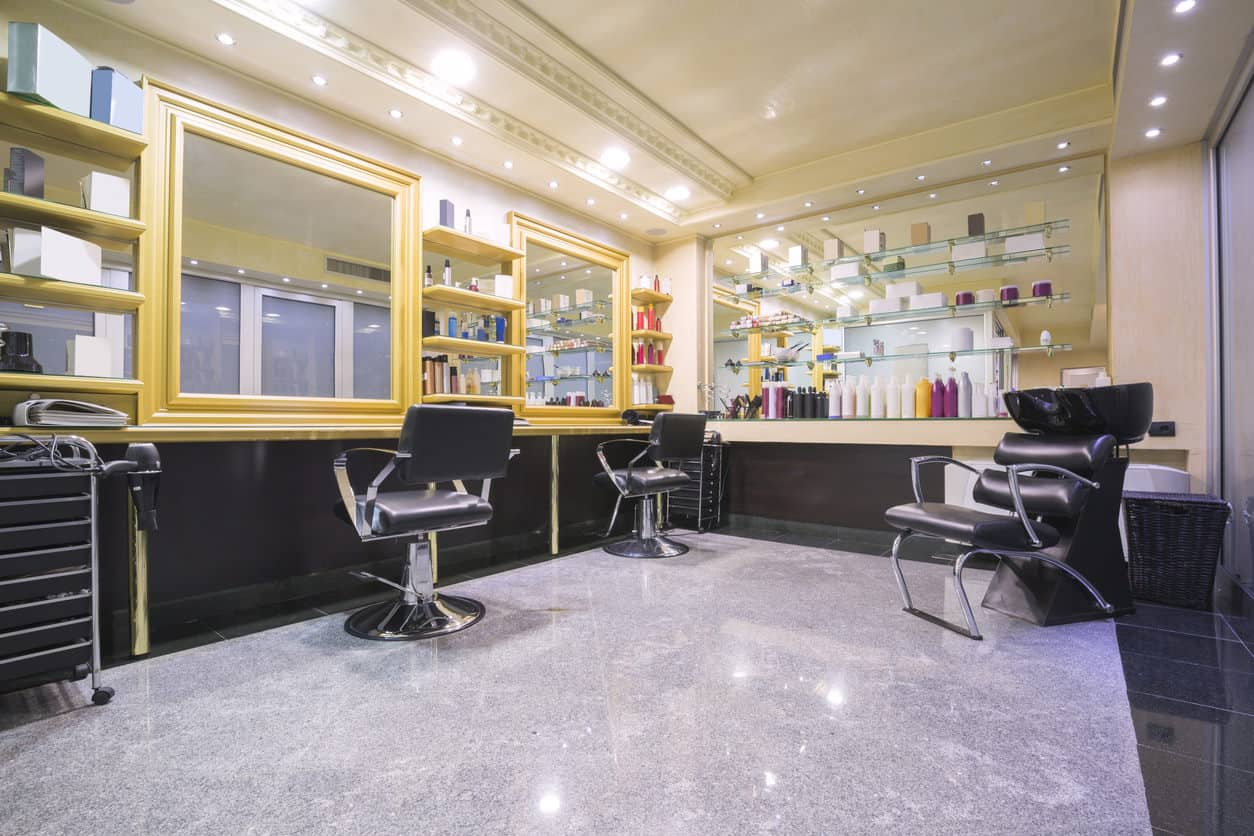 A raised ceiling accented by detailed trim adds some interest and opens up the room. Pale yellow walls and sunshine yellow frames around large mirrors and shelves brighten up this salon and offset the black chairs, dark tile, and dark wood. The glass shelves make them seem as if they are invisible and the colors of the products on them pop against the subtle yellow that's reflected by the mirror behind them.