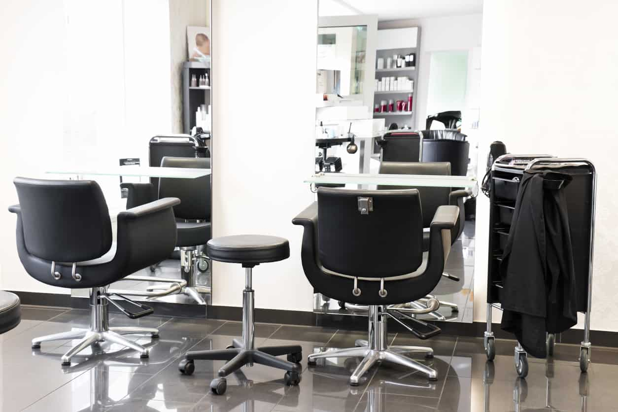 Mirrors that cover almost all of the wall expands the space in this salon. The white walls and glossy light grey floors are complimented by the black and stainless steel chairs. Grey shelves highlight the bright red of the product packaging.