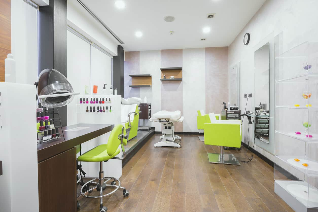 Neon yellow-green pops in this white and grey salon. Natural wood floors and accents and a striped accent wall make this Modern salon feels earthy and sophisticated, and the bright colors of the nail polish really stand out against the background. The soft glow of the lights is reflected by the large mirrors and stainless steel bases of the bright chairs.