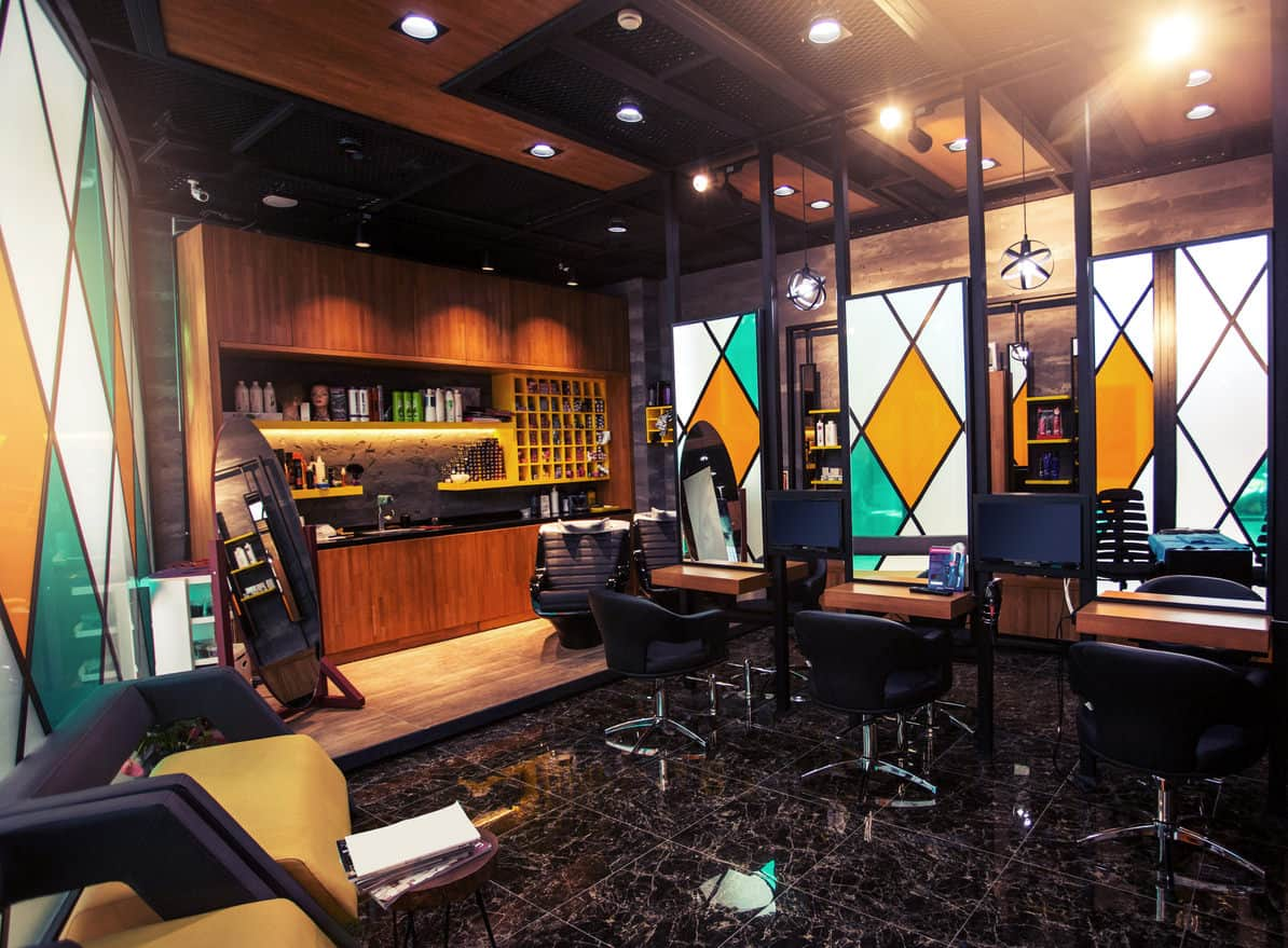 This salon features dark marbled tiled floor and rich wood cabinets and tables. Frosted white, yellow and teal diamond design of the stained glass offers a bold statement piece and compliment the wood nicely. The yellow and navy chairs and yellow shelves stand out against the dark marble and black countertop. This salon has the feel of a den or study, and you would expect customers to be lounging in their slippers and robe smoking a pipe. The metal globe pendant lights and an oval floor mirror are a nice touch. The black glossy marbled floor highlights the center of the room and adds to the richness of this salon.