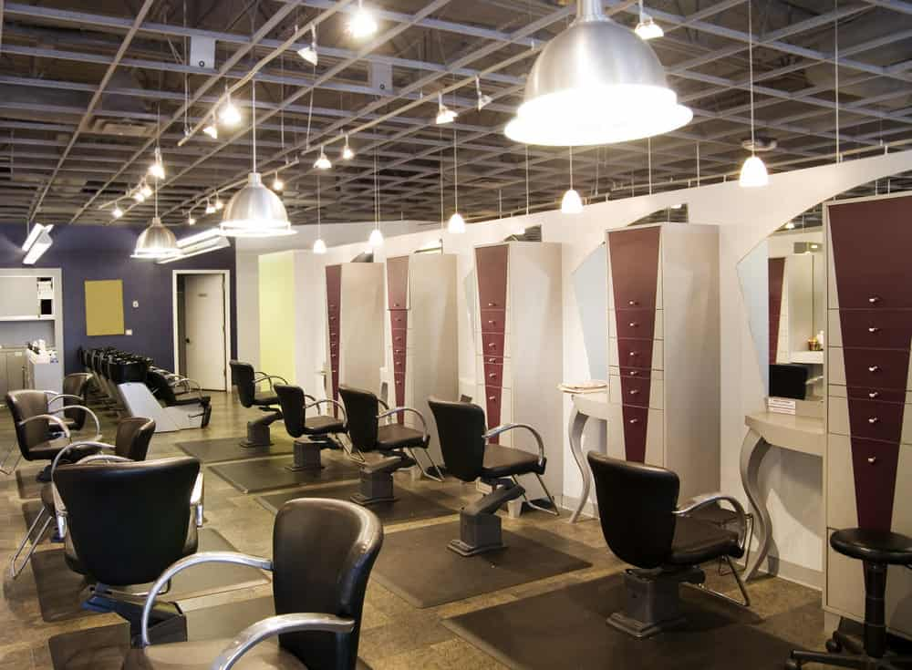 Numerous hanging stainless steel pendant lights brighten up this salon and highlight the black and stainless steel chairs. The Medium blue walls accent the maroon chevron stripe painted on the drawers with stainless steel knobs.