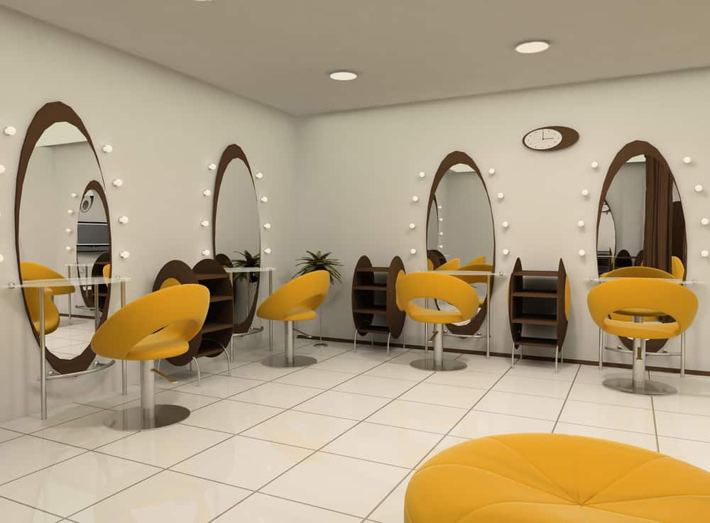 Futuristic yellow chairs and wood shelves stand out against the white walls and tile floor. Simple white bulbs frame each of the oval mirrors that are placed in front of the styling chairs. A bright yellow pouf looks bold against the large white tiled floor.