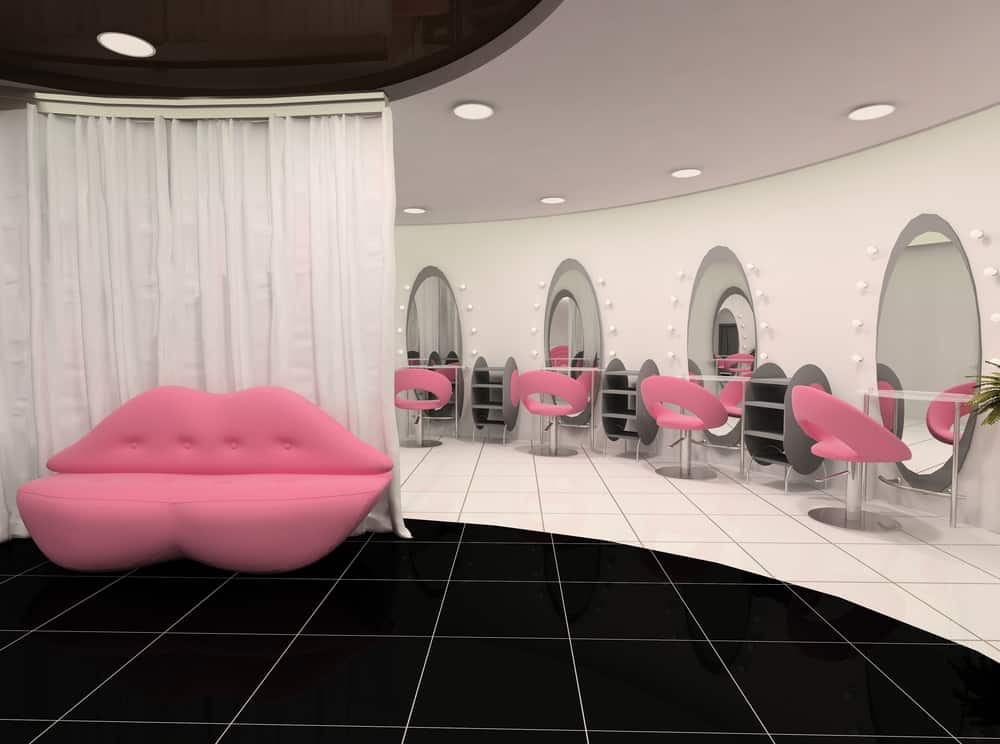 Fun bubblegum pink seating in the shape of lips greets customers when they visit this salon and the matching pink styling chairs really pop against the white walls and grey shelving. There is also a black tile accent on the floor that makes this salon very stylish and modern. The vanity lights around the oval mirrors stand out even when they are not lit.