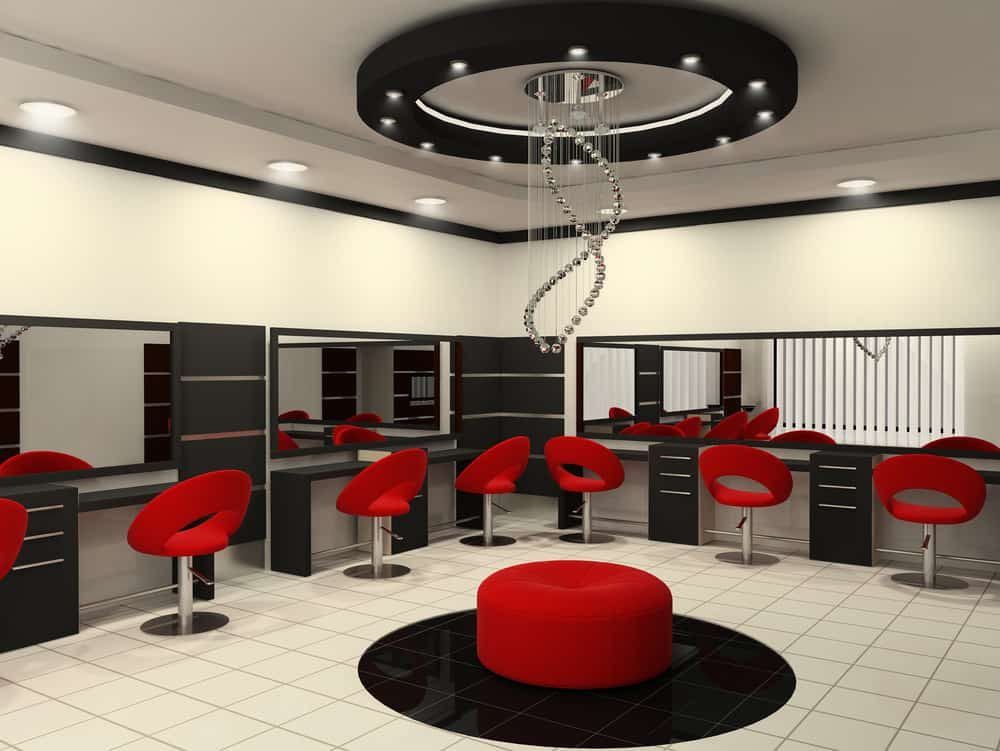 A delicate chandelier made of stainless steel orbs intricately designed to look like a strand of DNA is situated in the center of the room. It's inside a black disk that has small canister lights inside the ring. It's the centerpiece of this black, grey and white salon. The modern red chairs and ottoman really stand out against the sleek background and the black and white tile floors and shelves.