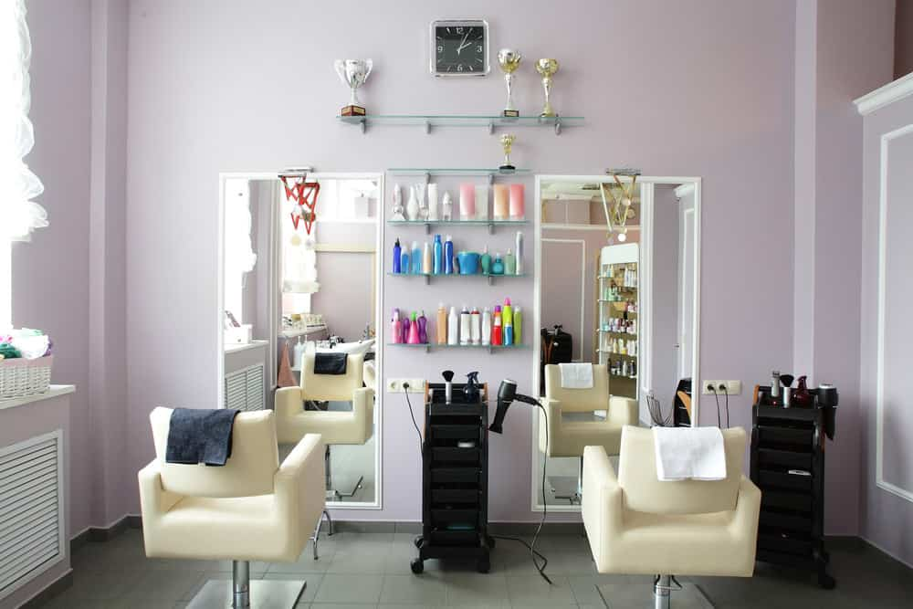Cream colored chairs and portable black carts stand out against the pale lavender walls and white trim. The colorful packaging of the products on the shelves and the sports memorabilia casually draws the eye to them.