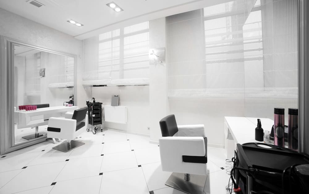 This almost entirely white salon has small accents such as the diamond pattern in the floor tiles and black sections of the stylist chairs. One wall is a mirror framed in a pale grey and the stainless steel base of the chairs add a hint of shine.