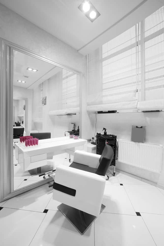 An almost all-white salon makes the rectangle tiles, portable cart, and pillow of the chair pop and draws the eye to the small details such as the blinds and the baseboard heater.