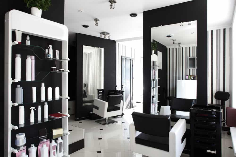 Crisp black and white salon really highlights the green of the plants and the pink and burgundy of the salon items. There is also grey in the striped wallpaper, and the mirrors open up the space and reflect the natural light.