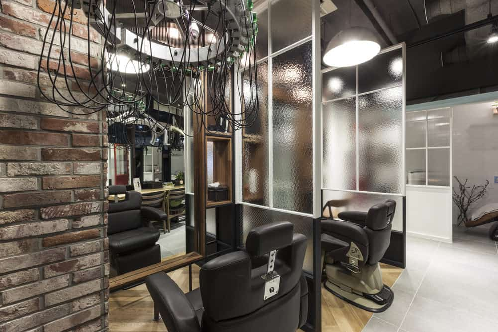 Interesting light fixtures immediately draws the eye upward, and the brick and textured window partitions create a relaxing and earthy feel. The soft black leather chairs and wood floor and accents inspire a calming atmosphere. A red door pops in the distance.