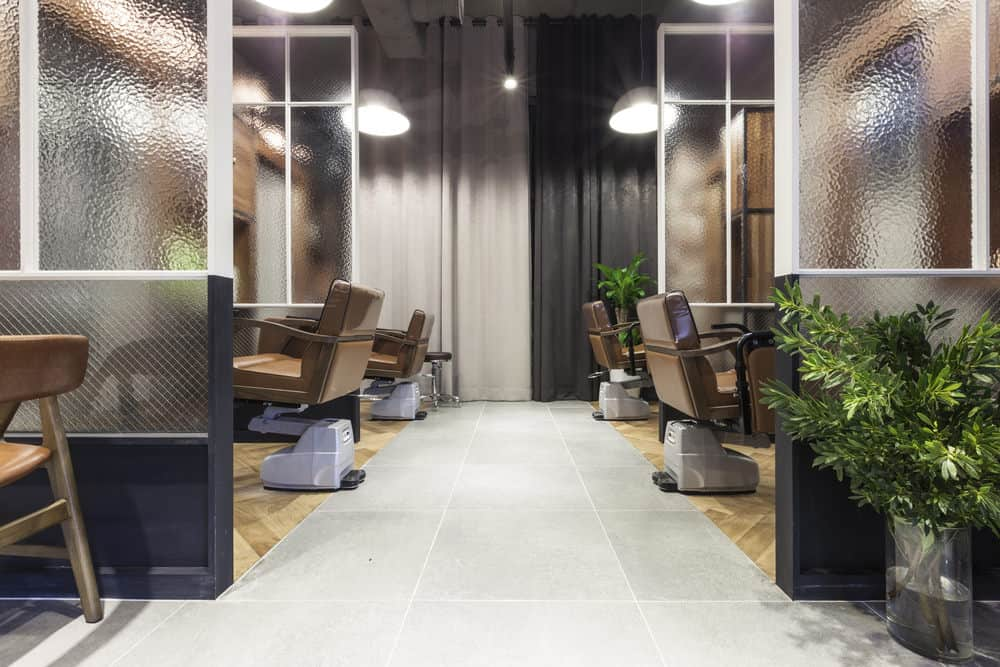 Metal pendant lights and black and white curtains balance the look of this salon, and the lush green plants create a relaxing Zen-like atmosphere.