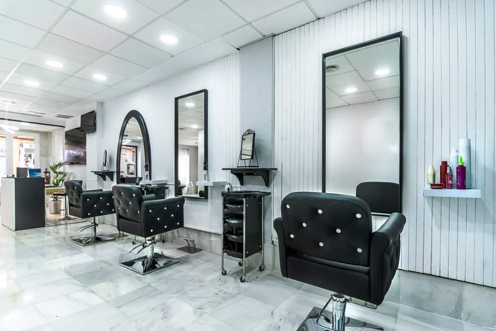A white beadboard wall and black framed mirrors paired with the black and white buttoned chairs. The simple white shelves hold colorful products and the glossy marbled tile floors make this salon super chic and modern.