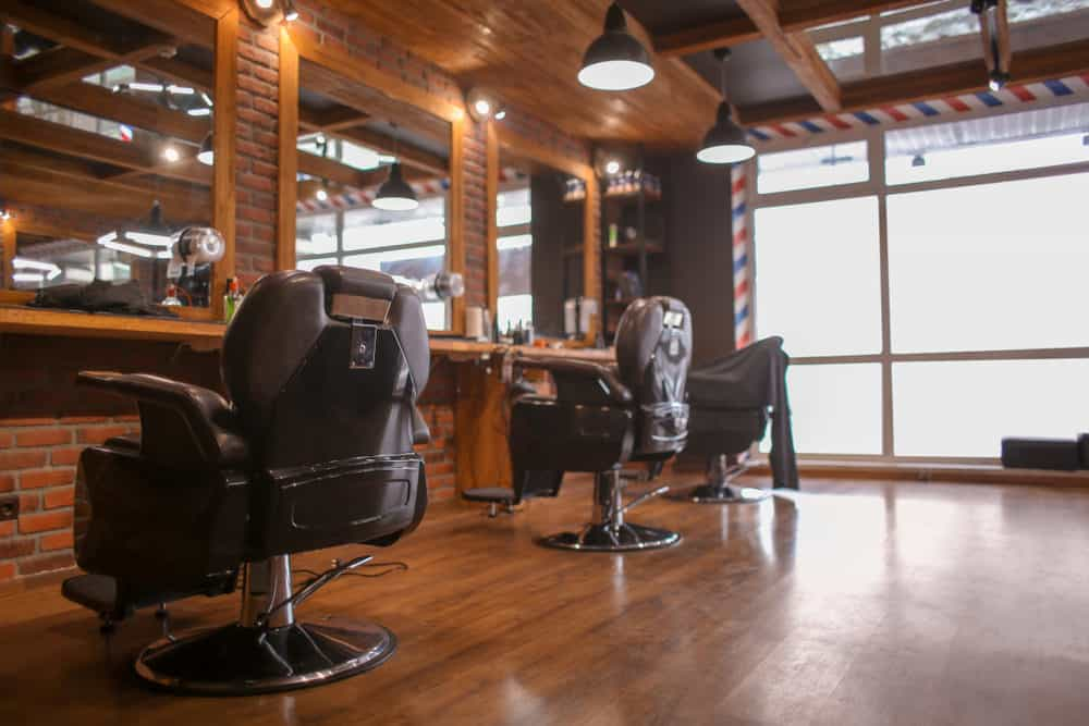 Warm brick walls and oak ceiling and floors with a hint of gloss create a warm and inviting environment. The famous barber pattern frames the large window, and the dark brown buttery leather chairs complement the vintage look of the hanging metal pendant lights.