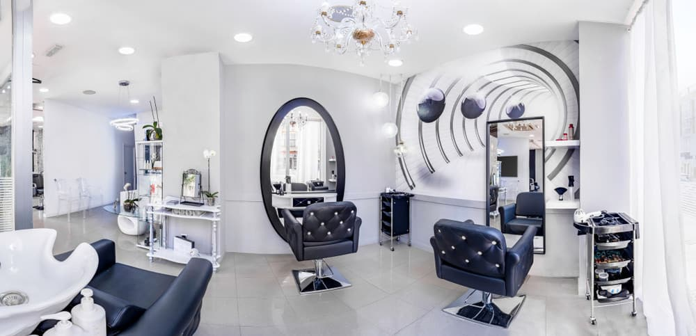 The gold and crystal chandelier draws the eye up to the ceiling, and numerous canister lights add a soft glow to the room. The futuristic mural on the wall behind one of the mirrors makes it seem as if the room goes on further and the black and white buttoned leather chairs look comfortable as well as stylish.