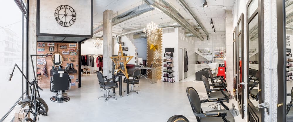 This spacious warehouse has many focal points. The gold brick wall, golden star mirror, antique bike, license plate memorabilia displayed on the natural brick wall and the pops of red and yellow all stand out against the mainly white and grey background. The black leather and studded chairs look vintage, and the track lighting gives this salon an industrial look.