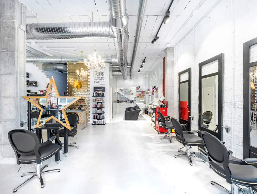 The shiny metal ductwork is as much as a focal point as the gold brick wall and the red tool cart. The track lighting stands out against the white ceiling, and the warm glow of the chandeliers make this industrial salon look inviting. The black and stainless steel chairs look inviting, and the open space seems like it stretches on forever.