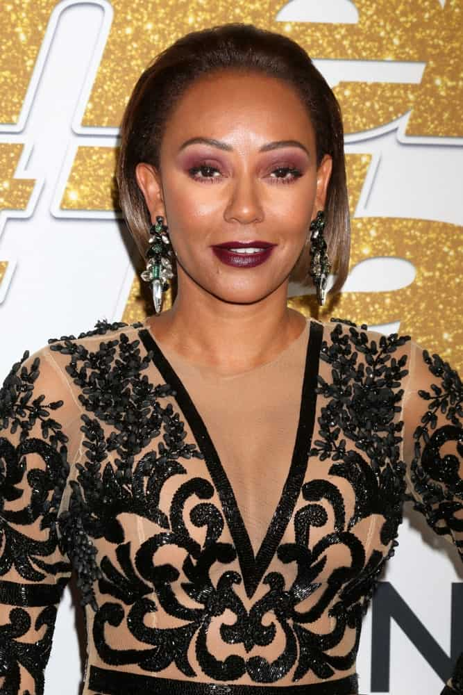 """Mel B arrived at the """"America's Got Talent"""" Season 13 Live Show Red Carpet on August 14, 2018, with a slicked bob. She finished the look with dark red lipstick, smokey eyes, and statement earrings."""