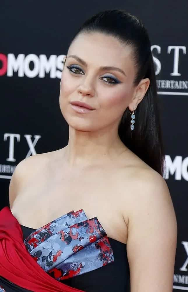 The stunning Mila Kunis wore her raven medium-length locks in a slick ponytail hairstyle that complemented her elegant neckline at the Los Angeles premiere of 'Bad Moms' on July 26, 2016.