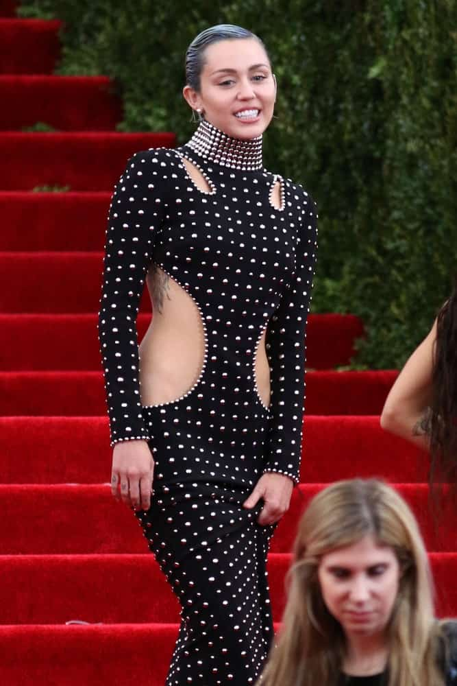 Miley Cyrus attended the Costume Institute benefit gala at the Metropolitan Museum of Art on May 4, 2015 in New York. She wore a lovely long black dress incorporated with metal studs that went well with her slicked back dark pixie hair.