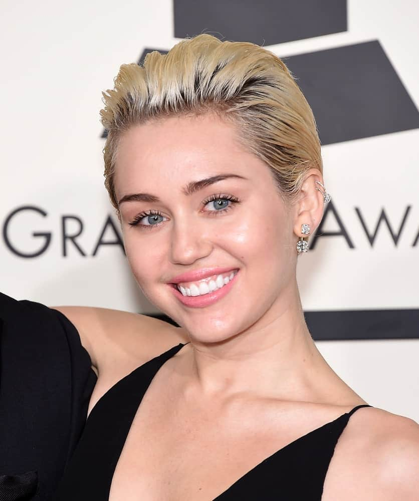 Miley Cyrus sported a slicked back highlighted blond pixie hairstyle to pair with her sexy black dress and bright smile at the Grammy Awards 2015 on February 8, 2015 in Los Angeles, CA.
